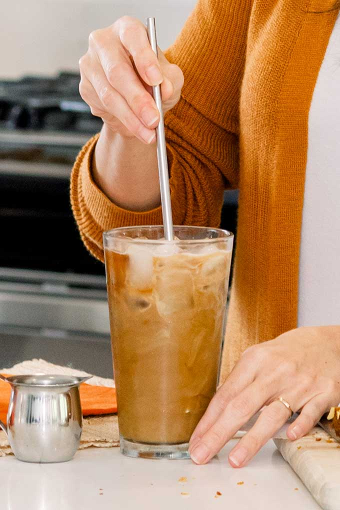 image: side view stirring cream into instant iced coffee with a straw