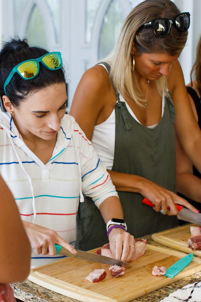 image: Women with cutting boards cutting beef chunks for kabobs side by side.