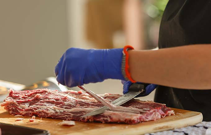 image: closeup view of hands slicing fat off a cut of beef.