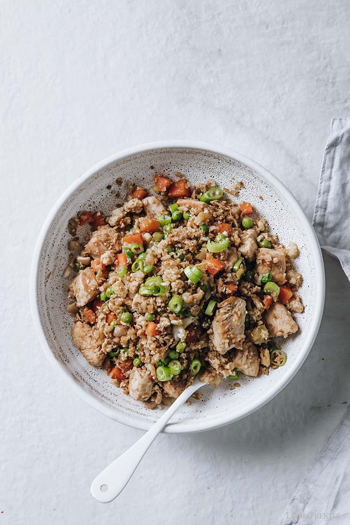 image: overhead view of white bowl filled with chicken fried cauliflower rice