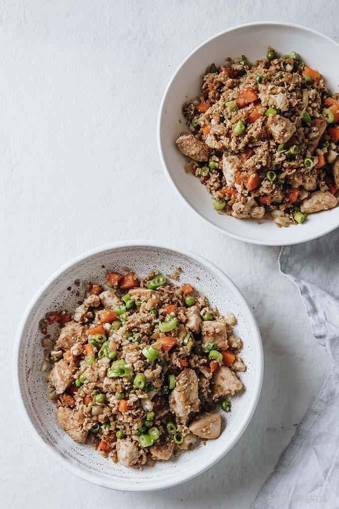 image: two bowls filled with chicken fried (cauliflower) rice.