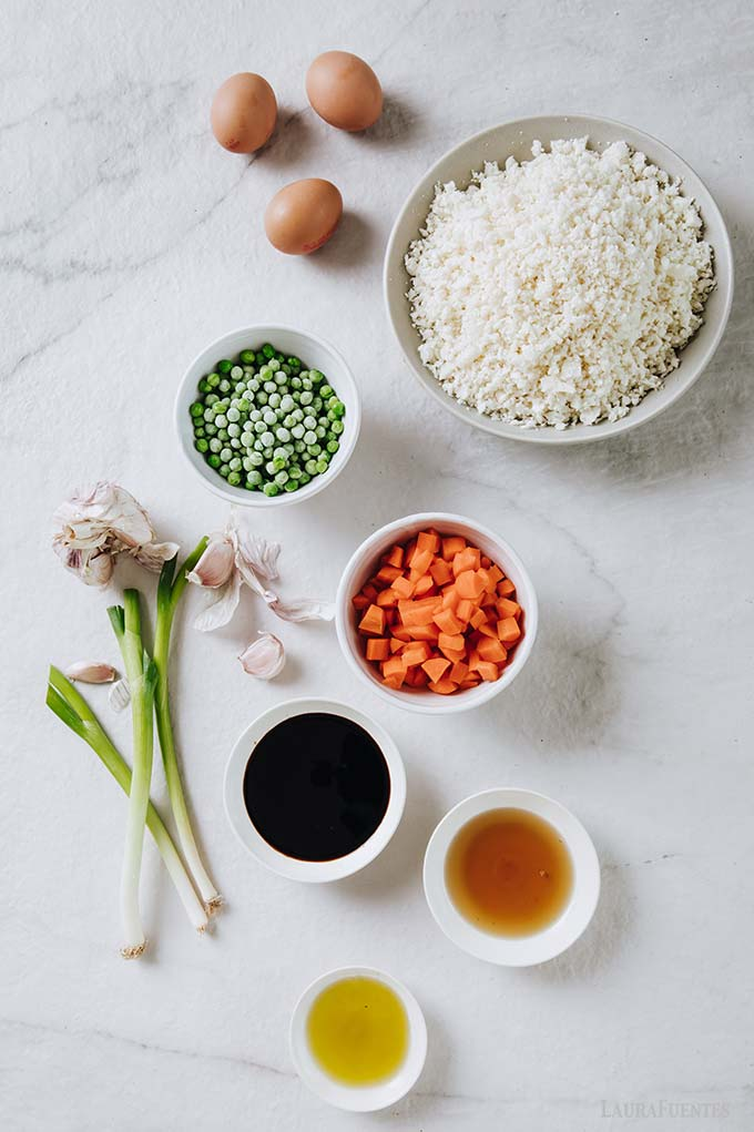 image: ingredients for cauliflower fried rice in small white bowls on a countertop. Including cauliflower rice, scallions, chopped carrots, soy sauce, peas, brown eggs and sauces.