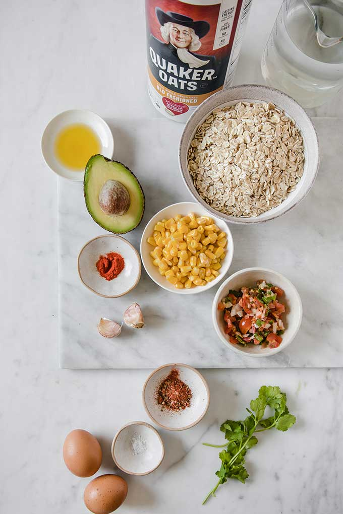 image: overhead view of ingredients laid out for savory summer oatmeal including oats, garlic, eggs, spices, avocado, corn and salsa.