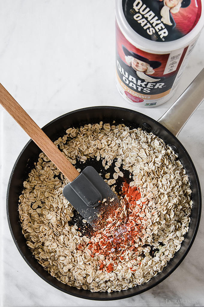 image: overhead view of oats in a skillet being toasted with spices.