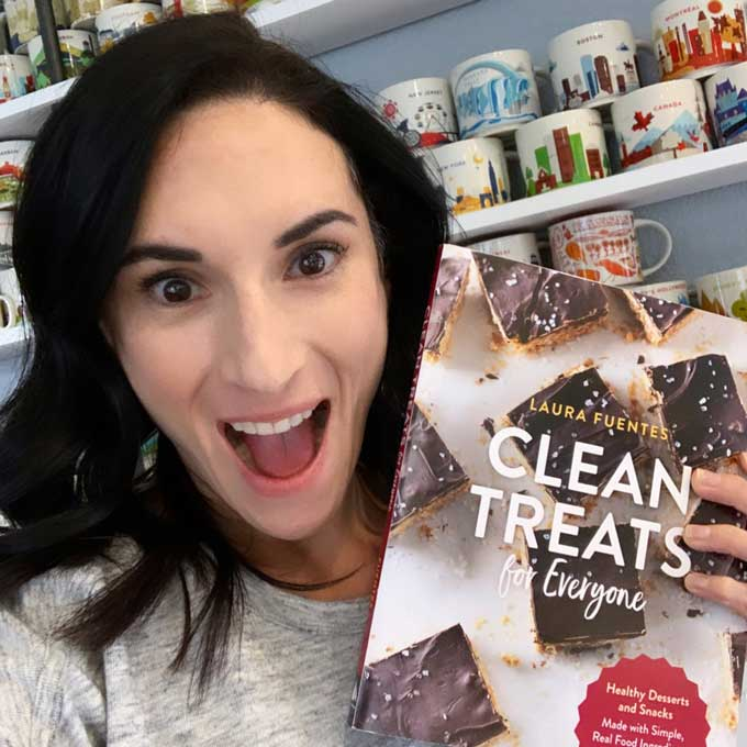 image: Laura Fuentes holding up copy of Clean Treats cookbook.