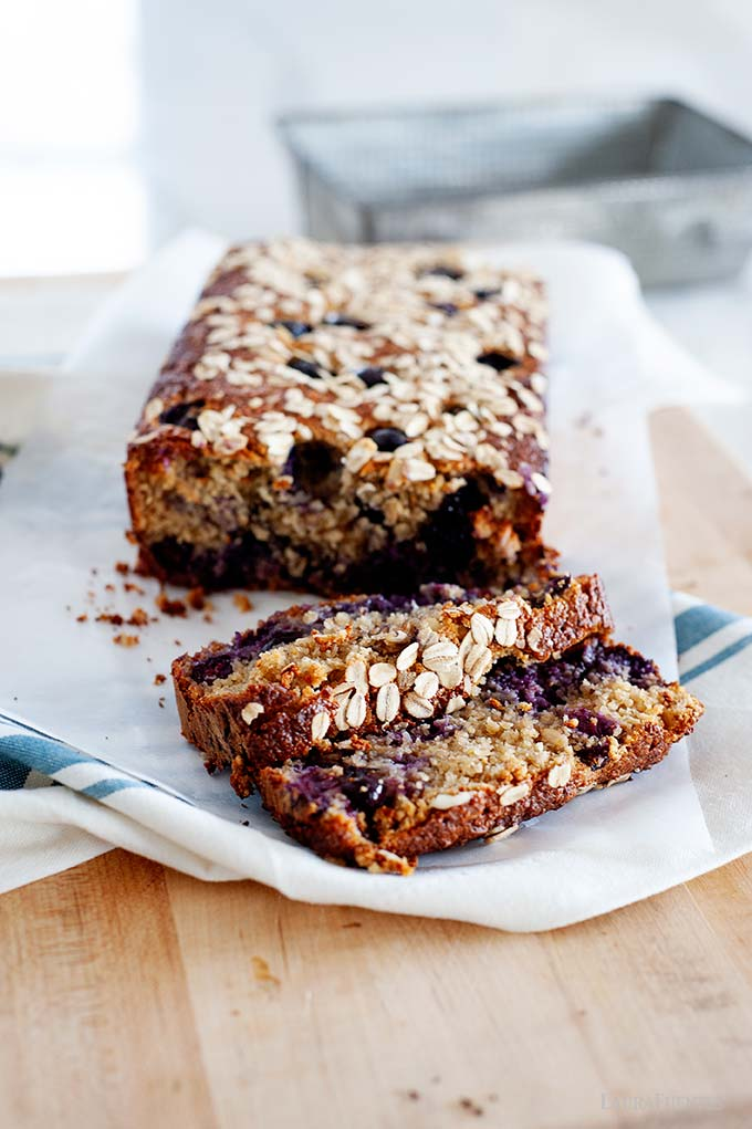image: loaf of breakfast bread with blueberries and oats on a cutting board. Two slices cut and placed in front. Loaf pan in the background of the image.