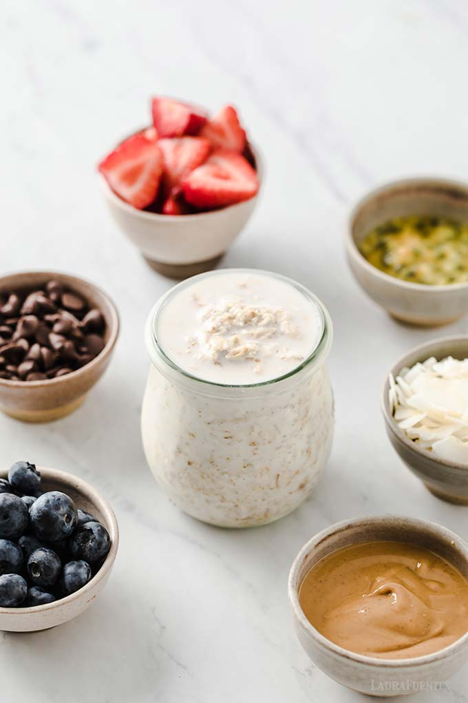 image: small glass jar filled with oats and milk. Six small bowls with toppings surround the jar. Including blueberries, chocolate chips, sliced strawberries, shaved coconut and peanut butter.