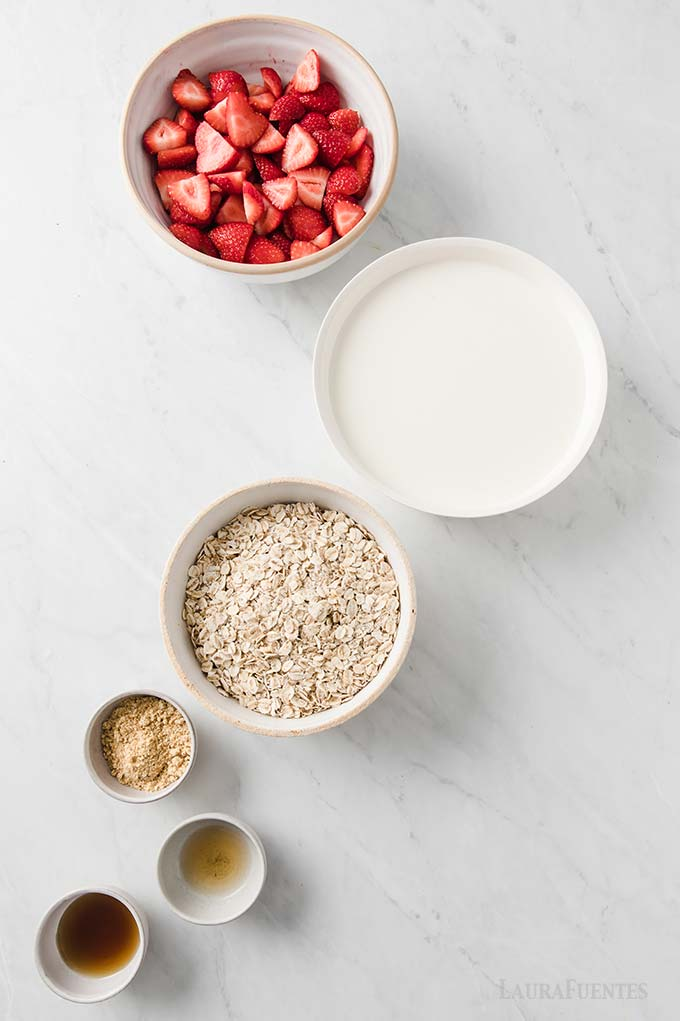 image: small bowls of ingredients for strawberry overnight oats lined up diagonally on a countertop.