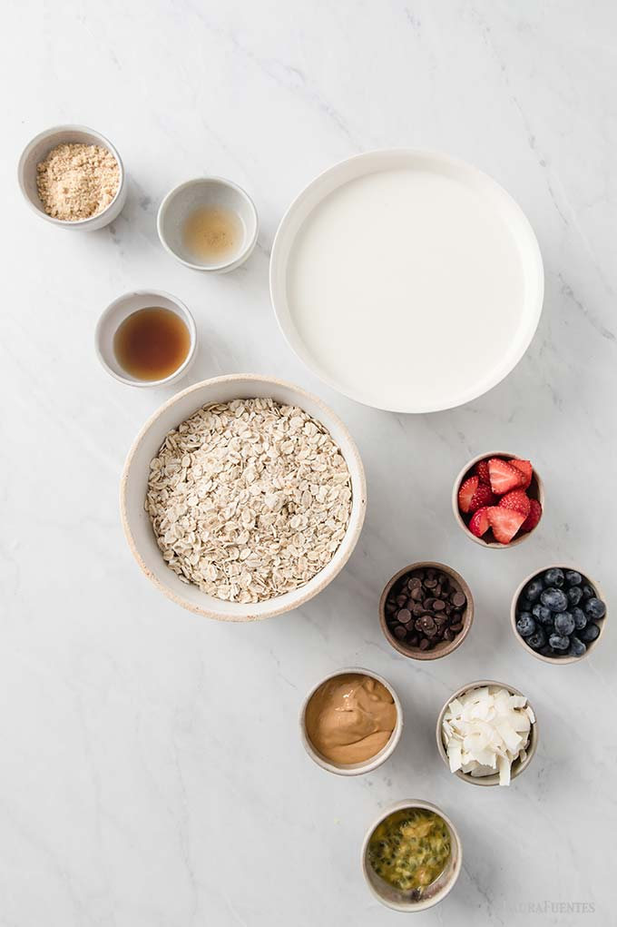image: toppings and ingredients  laid out in bowls on a counter top. Including large bowl of oats, and milk. Small bowls of brown sugar, chocolate chips, shaved coconut, fruit, and more.