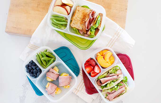 image: 3 lunches made with deli ham served with fruit and veggies inside lunch containers.
