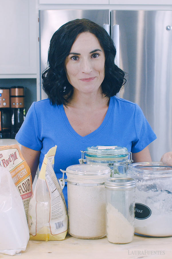 image: Laura standing in the kitchen with various flour containers and bags in front of her on the countertop.