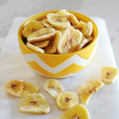 small yellow bowl filled with banana chips.