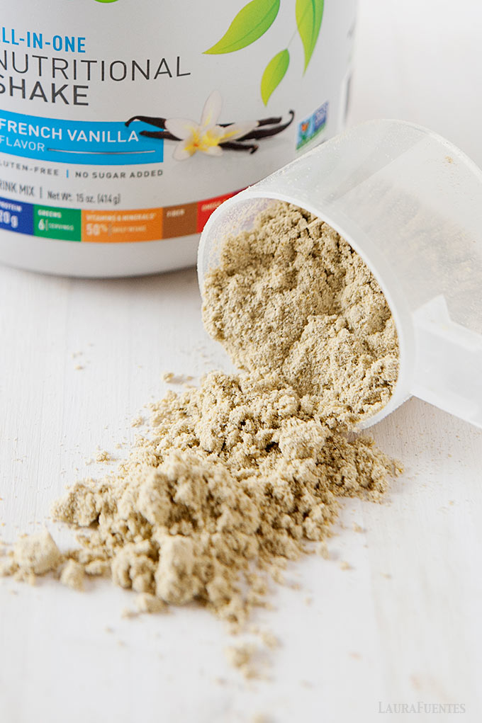 image: vanilla protein powder scoop spilling out onto a countertop. Large jar of powdered protein in the background.