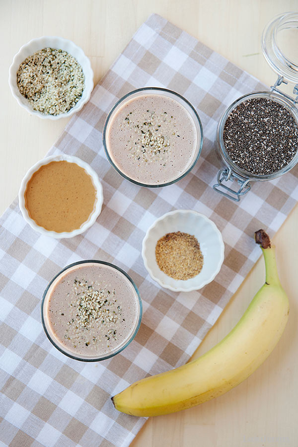 image: overhead view of two protein smoothies with chia seeds on top. Small dishes of smoothie ingredients, and a banana to the side of the smoothie glasses.
