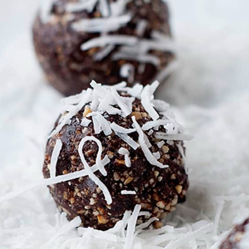 two chocolate energy bites rolled in coconut shavings