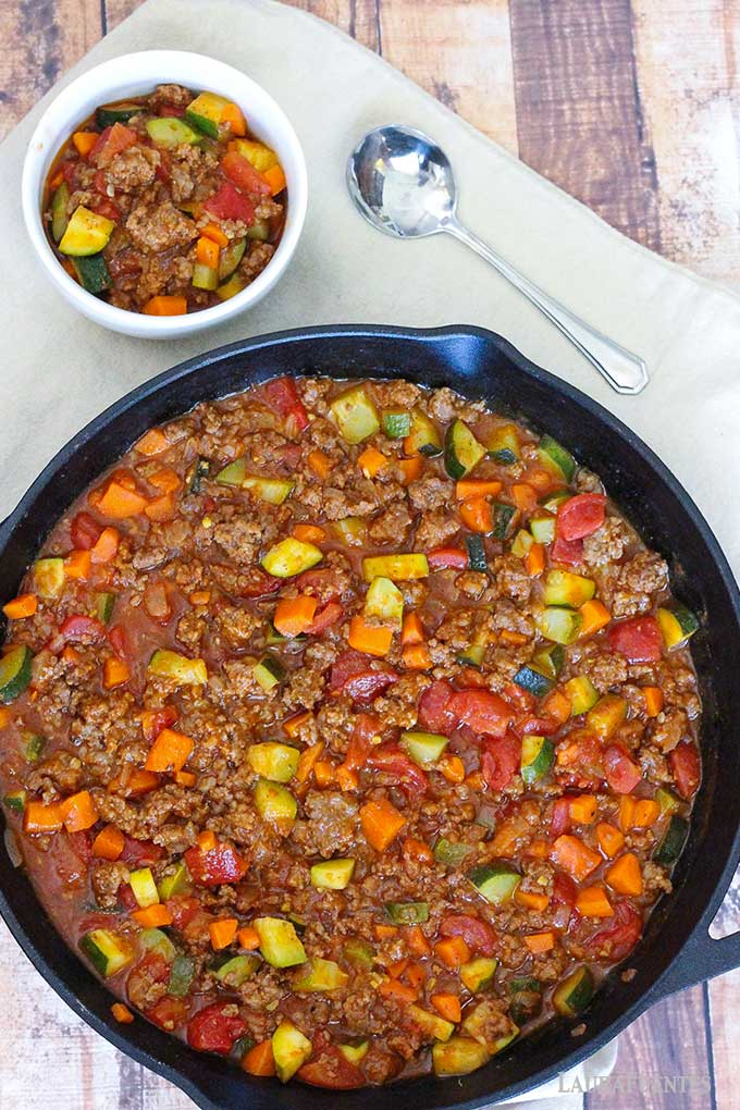 image: cast iron skillet full of meat and vegetable chili. Small white bowl of chili to the side of the skillet.