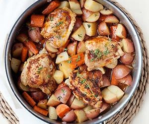chicken thighs, potatoes and carrots in a skillet
