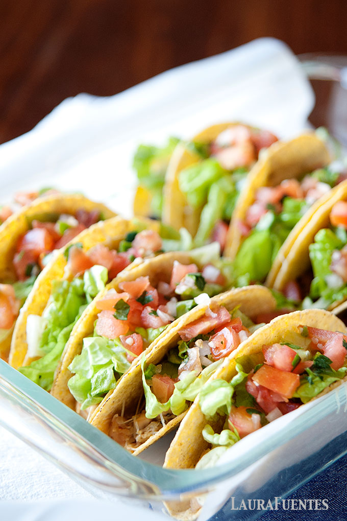 image: 10 hard shell tacos in a baking dish