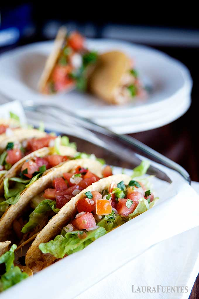 image: closeup of hard shell tacos in a baking dish. Two tacos on a plate in the background.