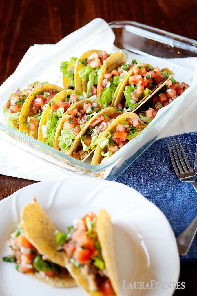 image: glass baking dish filled with baked chicken tacos next to a plate topped with two crunchy tacos.
