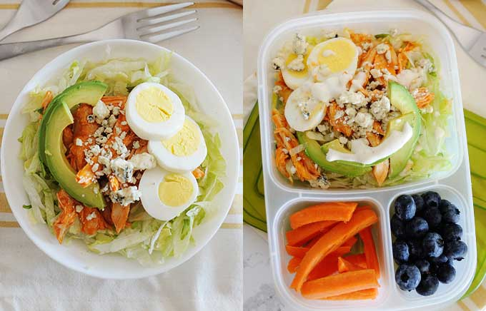 image: buffalo chicken with avocado, blue cheese crumbles, and a hard boiled egg on top of shredded lettuce in a bowl. The same ingredients inside a lunch container with blueberries and carrots on the side.