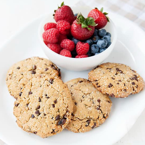 four large breakfast cookies on a plate with berries