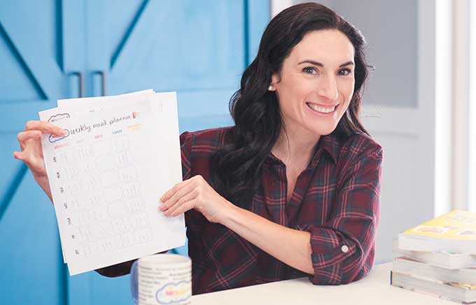 img: Laura in kitchen holding up meal prep printable plan