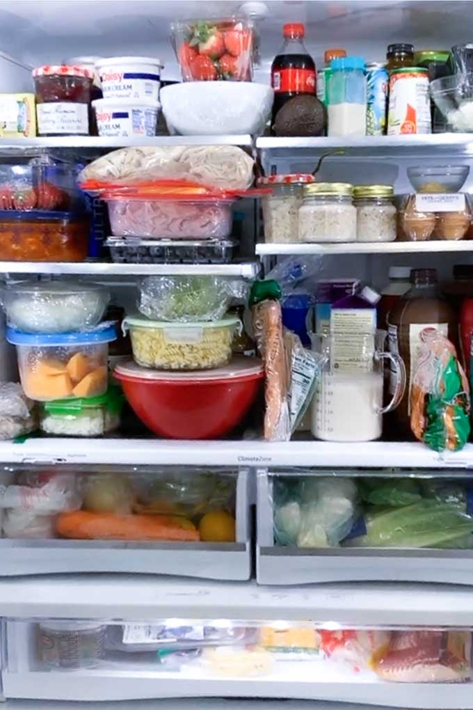 image: fridge full of produce, milk and meal prep ingredients.