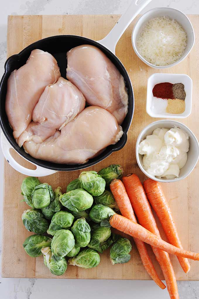 four chicken breasts in a skillet, and ingredients laid out on a wooden cutting board including carrots, brussels sprouts, small dish of mayonnaise, spices and shredded cheese.