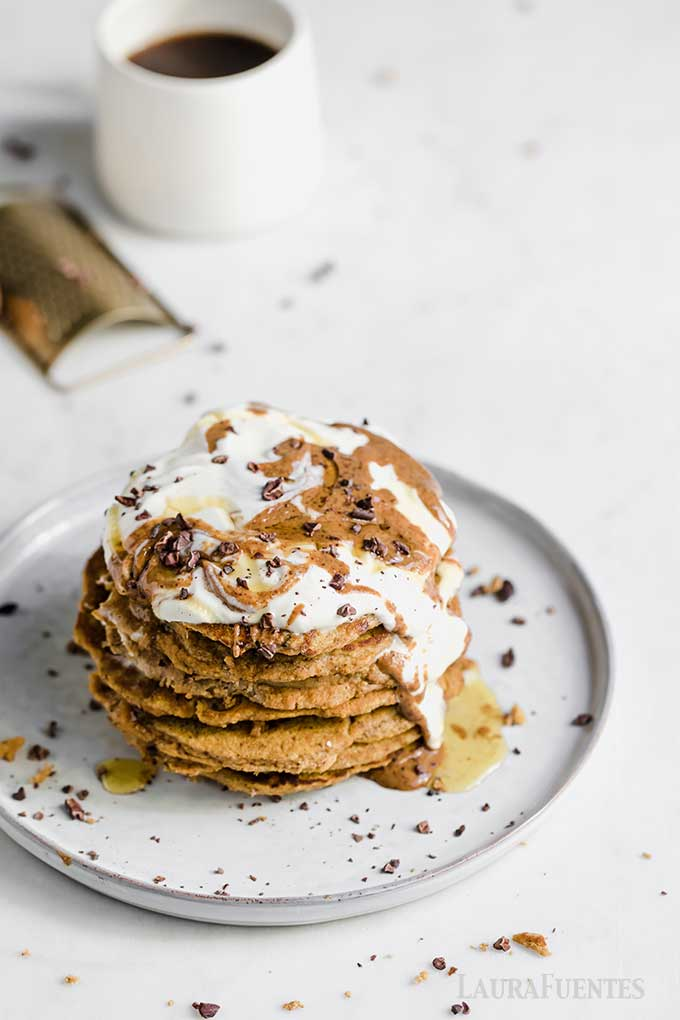 image: overhead view of talk stack of pumpkin spice pancakes with whipped cream and chocolate shavings.