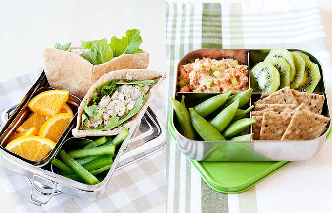 img: pita stuffed with salmon salad in a lunchbox. salmon salad with crackers and green veggies in a lunchbox.
