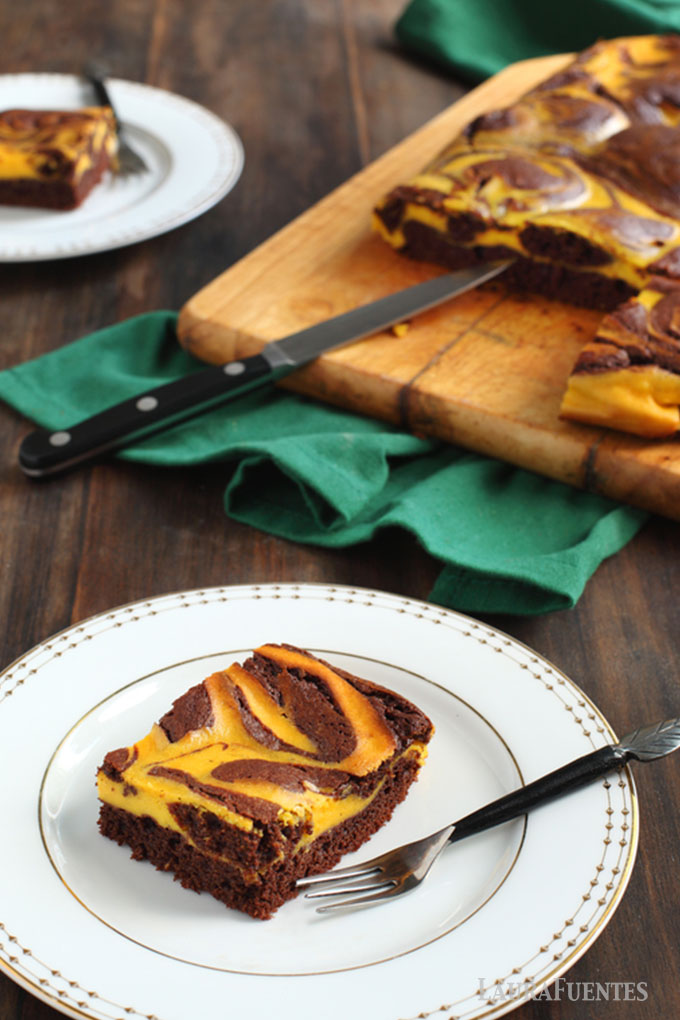 two plated pumpkin swirl brownies with larger amount of brownies on a cutting board in background