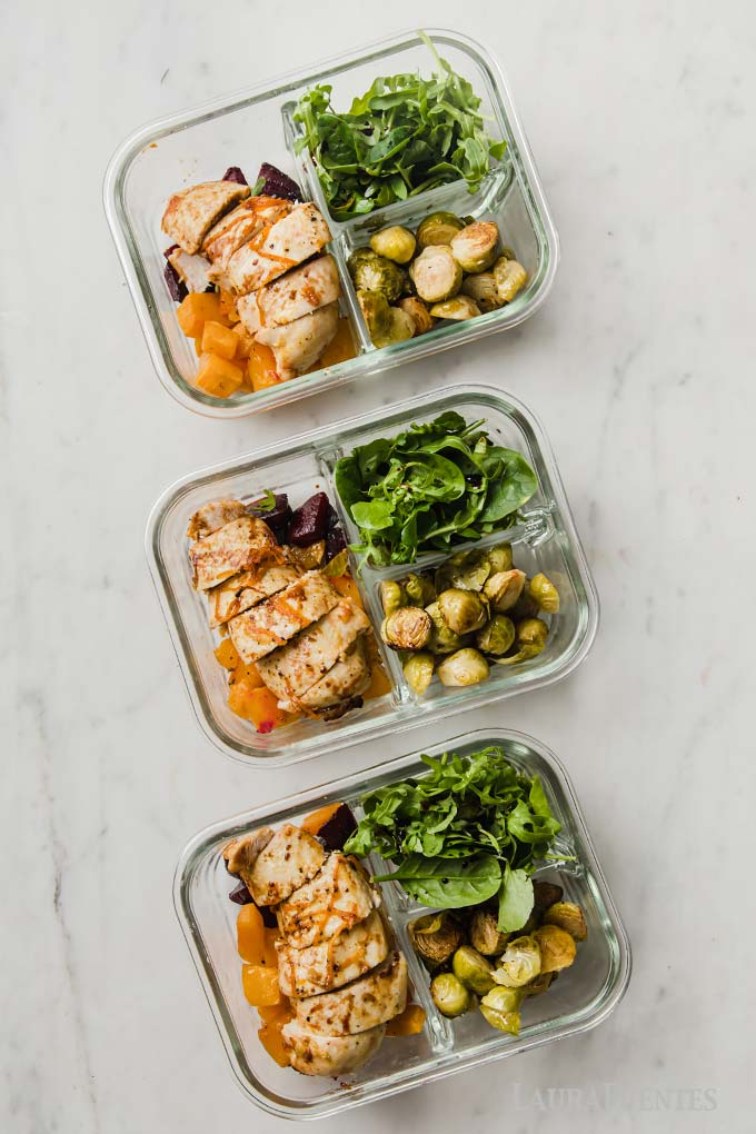 three lunch prep containers with sliced chicken, roasted vegetables and salad greens