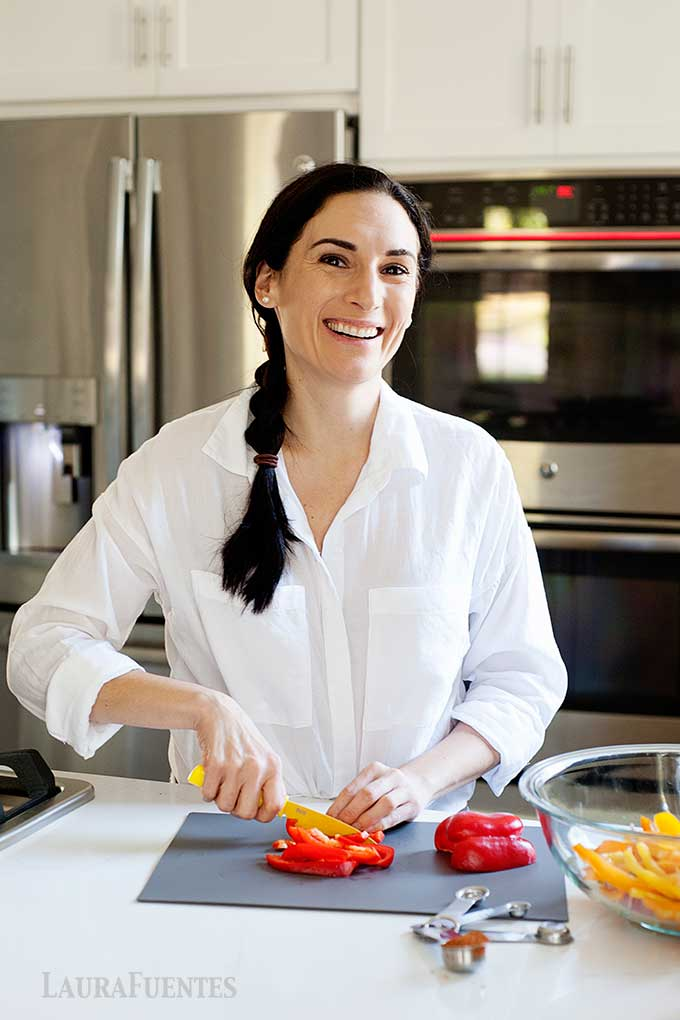 Laura standing in kitchen cutting red bell peppers into slices