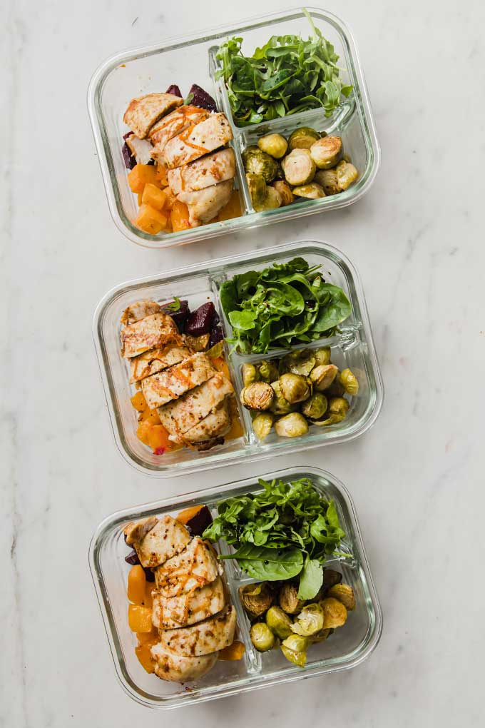 three glass lunch containers filled with sliced baked chicken and roasted vegetables