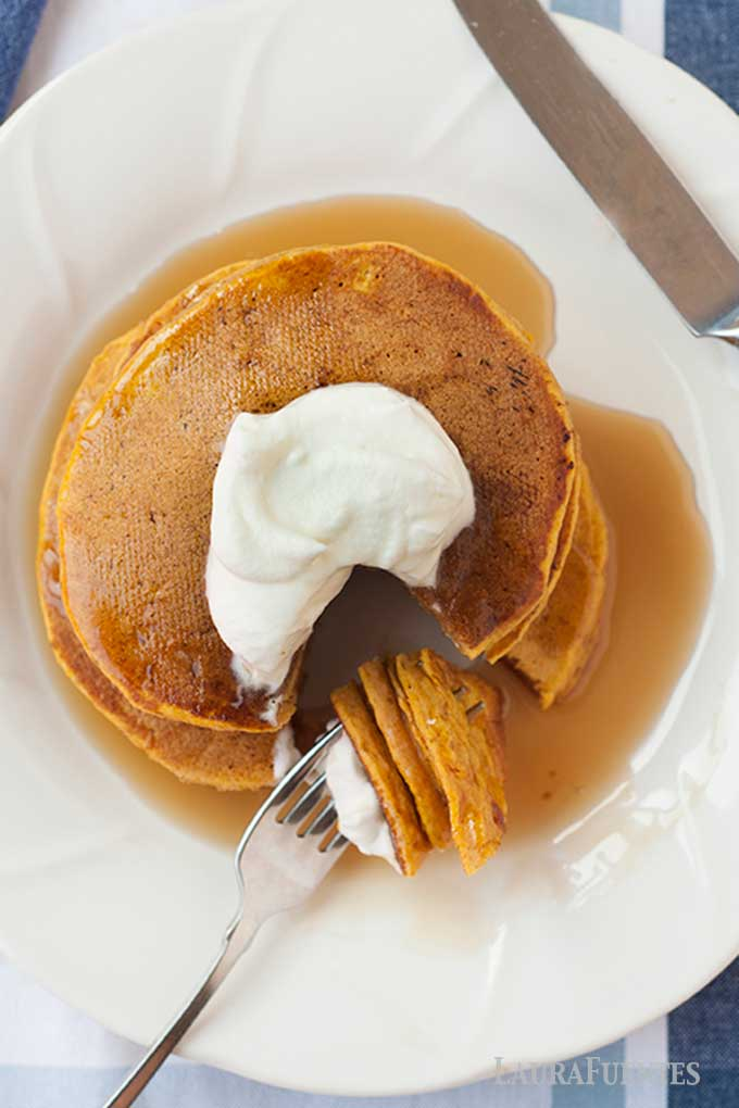 overhead view of sweet potato pancake stack topped with whipped cream and syrup