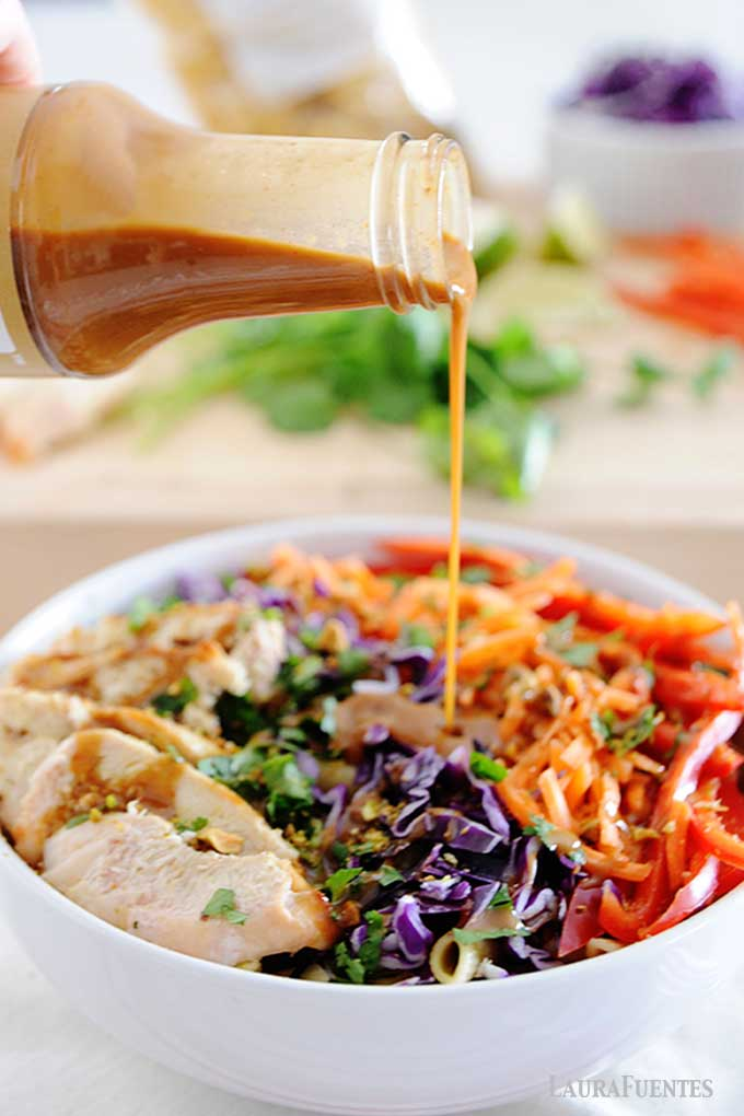 peanut sauce being poured from jar into a bowl of thai chicken pasta salad