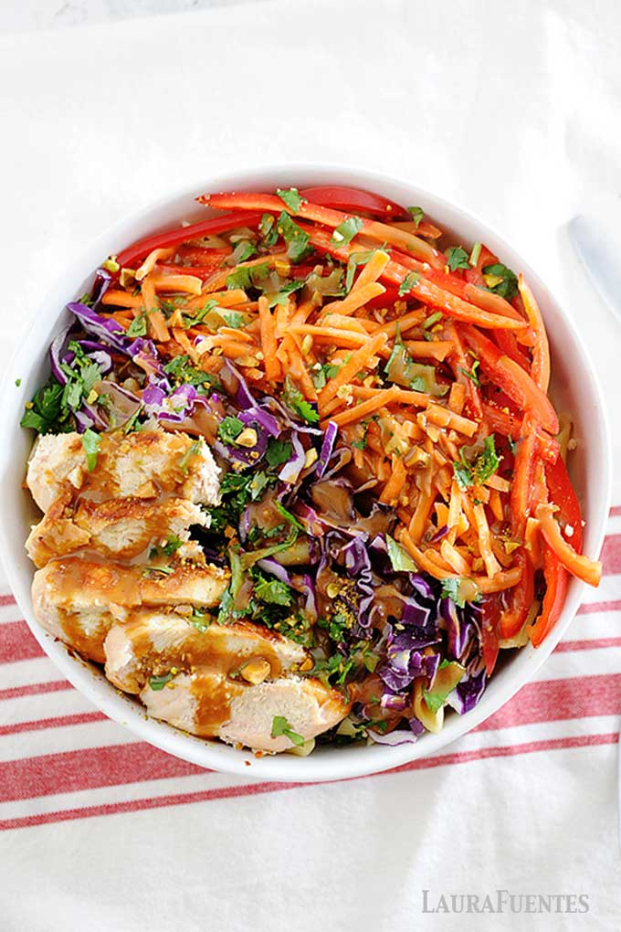 overhead view of large bowl of thai chicken pasta salad topped with peanut sauce