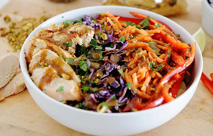 pasta salad in a bowl topped with sliced chicken, thai peanut sauce and shredded vegetables