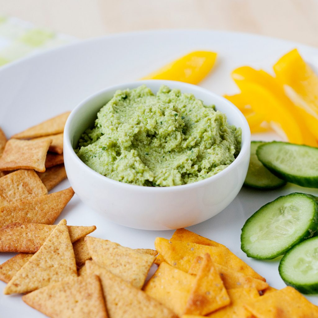 edamame hummus in a bowl with various snacks