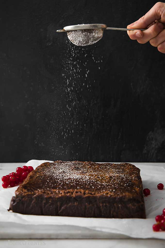 sprinkling powdered sugar over a square cake from a mini sifter