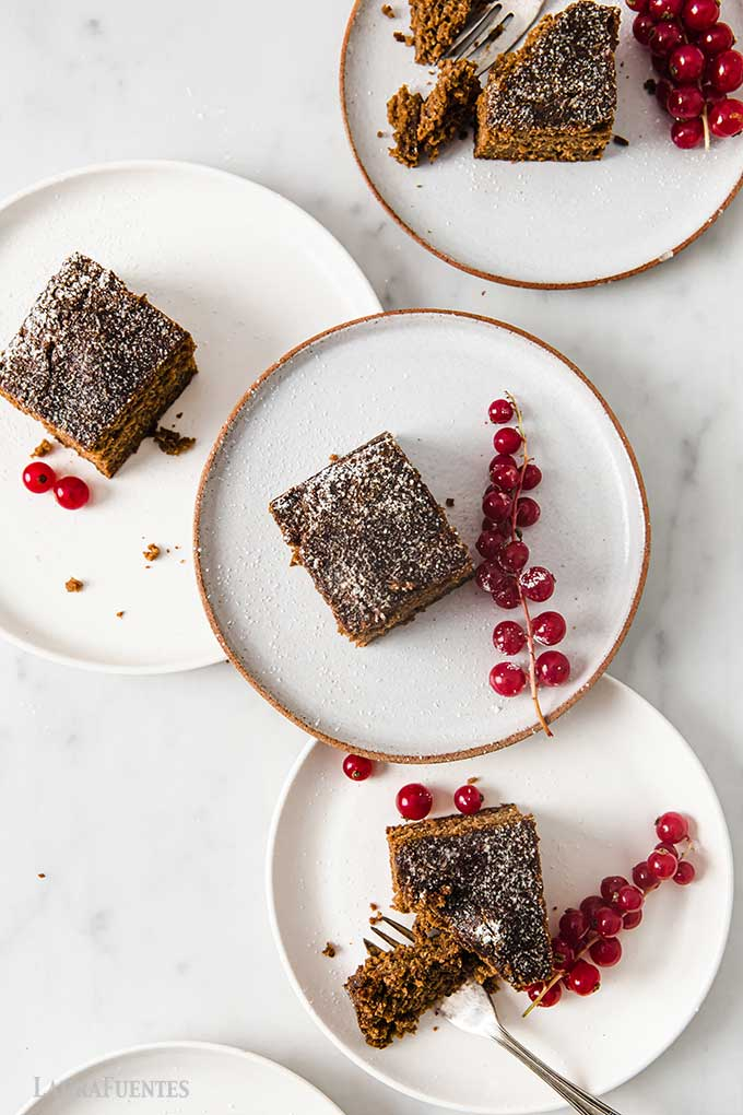 four plates of gingerbread cake topped with powdered sugar