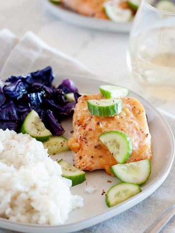 plate of salmon, topped with zucchini slices net to rice and bed of purple cabbage