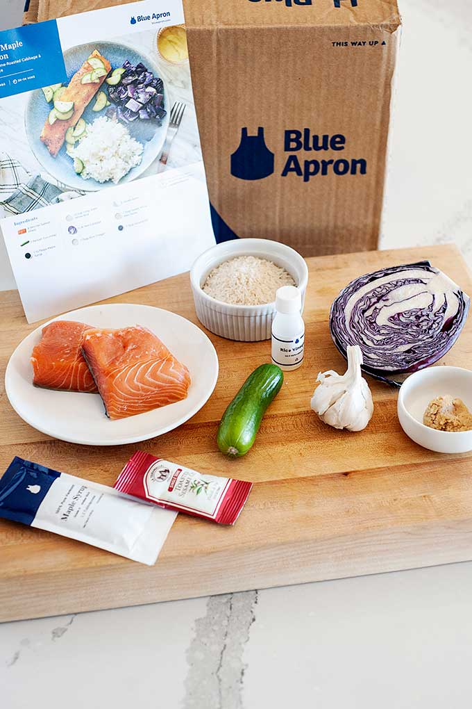 blue apron box and recipe card on a countertop, ingredients for miso salmon laid out in front of the box