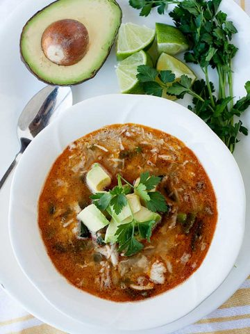 overhead view of chicken chili in a bowl topped with avocado cubes. Half an avocado next to bowl