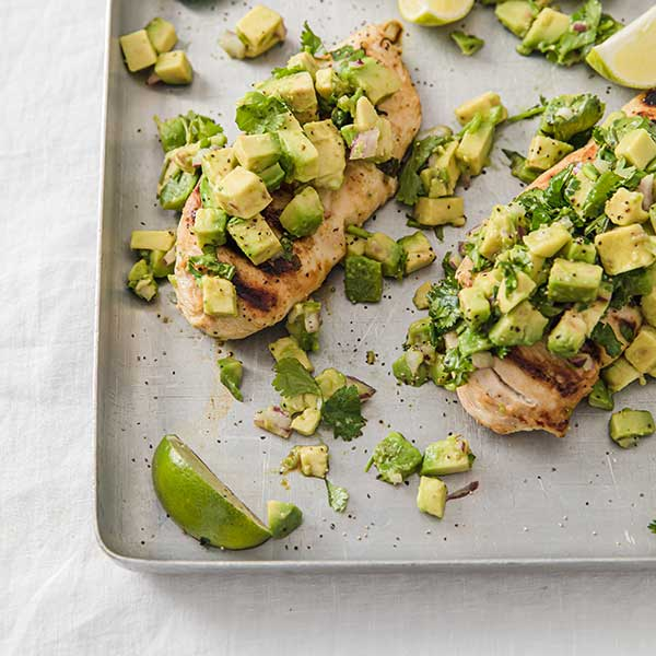 sheet pan of chicken topped with avocado salsa