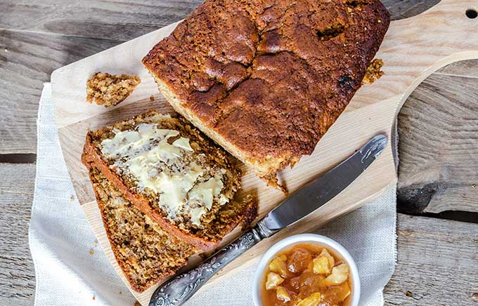 overhead look at half a loaf of applesauce bread, partially sliced with butter topping