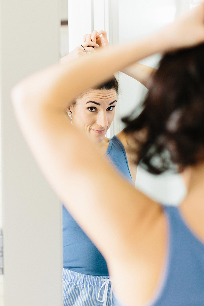 Laura looking in mirror putting up her hair