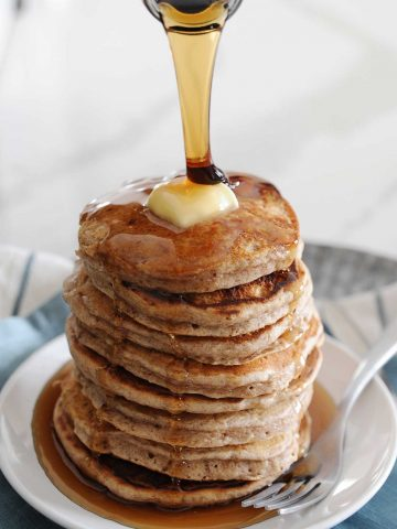 large stack of pancakes with homemade syrup being poured over the top