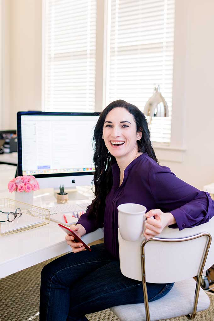 Laura at computer desk with cup of coffee and phone in hand